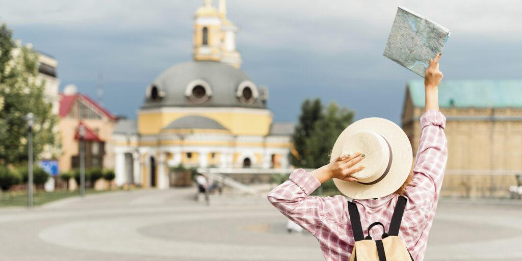 uma mulher de costas visualizando um mapa e segurando seu chapéu - Os tipos de intercâmbio e sua importância