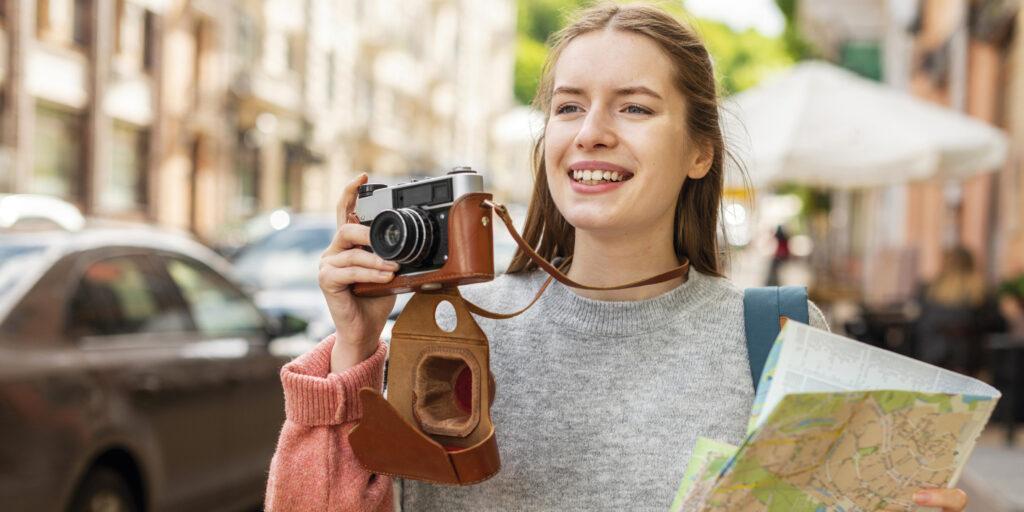 uma mulher sorrindo e segurando uma câmera de foto e um mapa - Os tipos de intercâmbio e sua importância