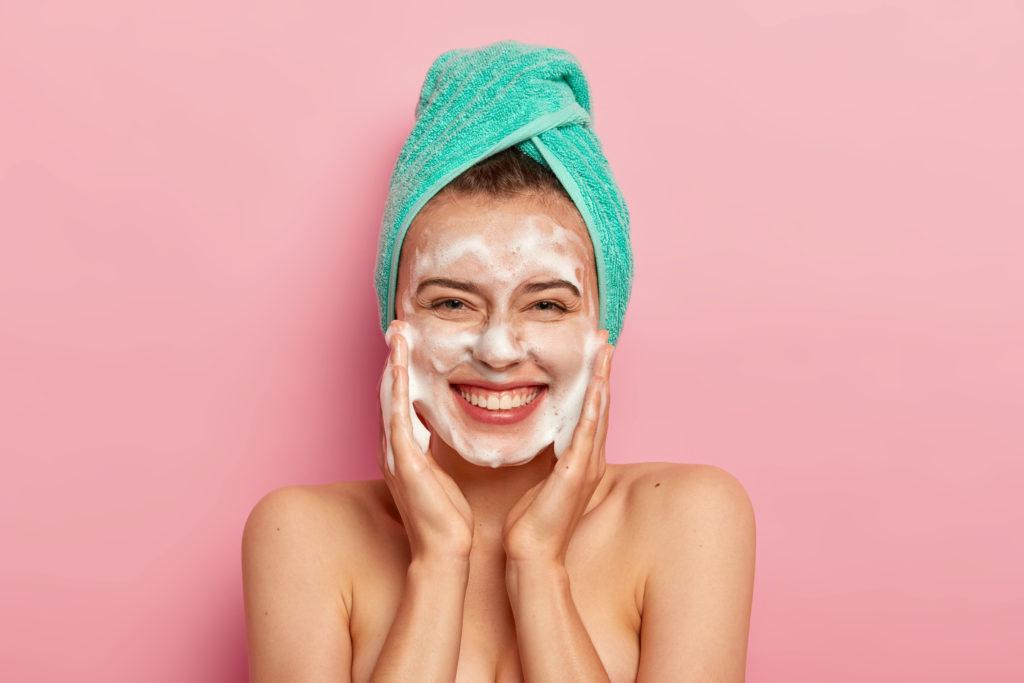 Mulher feliz fazendo a sua limpeza de pele