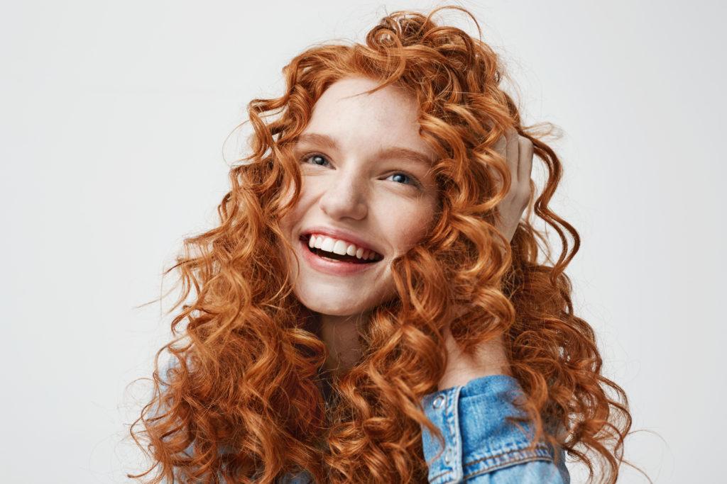 Mulher feliz com cabelo cacheado