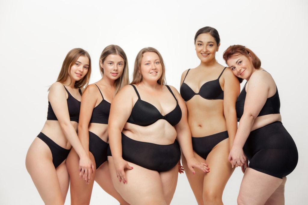 5 mulheres com corpos diferentes dando as mãos felizes