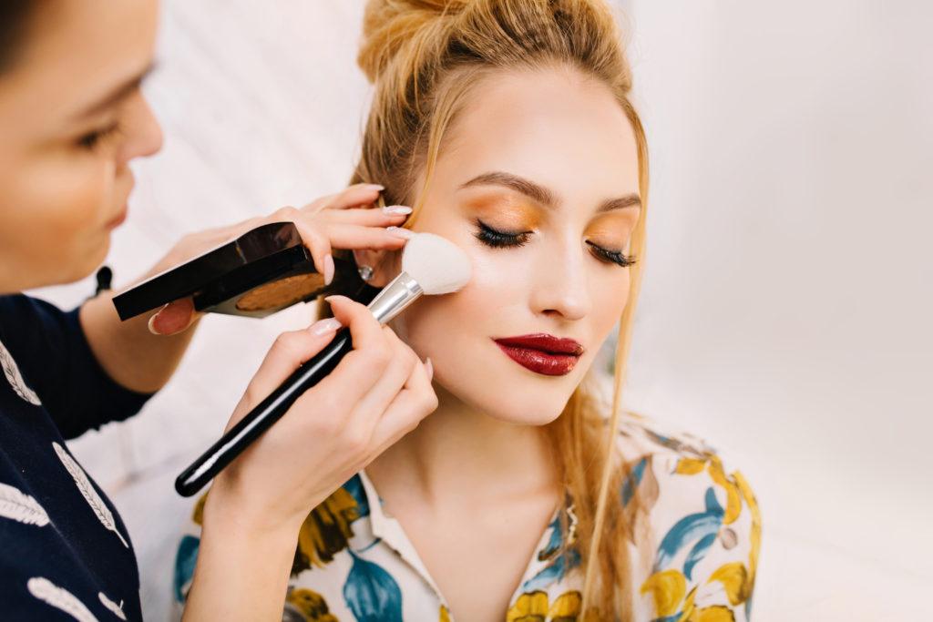 #DescriçãoDaImagem: mulher jovem fazendo maquiagem profissional