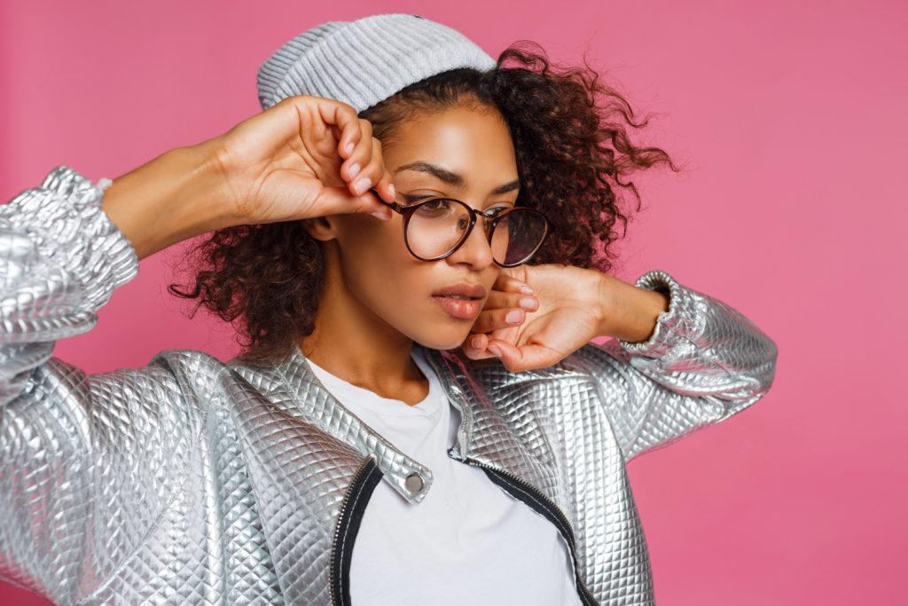 Mulher vestindo touca óculos de grau e jaquetas prateadas