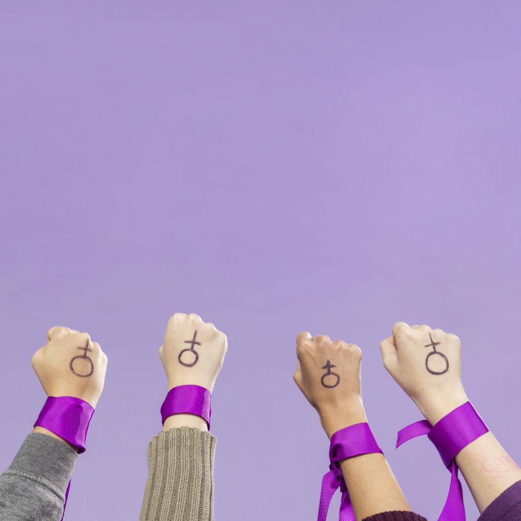 fundo lilás com 4 braços em primeiro plano com punhos fechados, fitas roxas amarradas e o símbolo de feminino desenhado nas costas de cada mão.