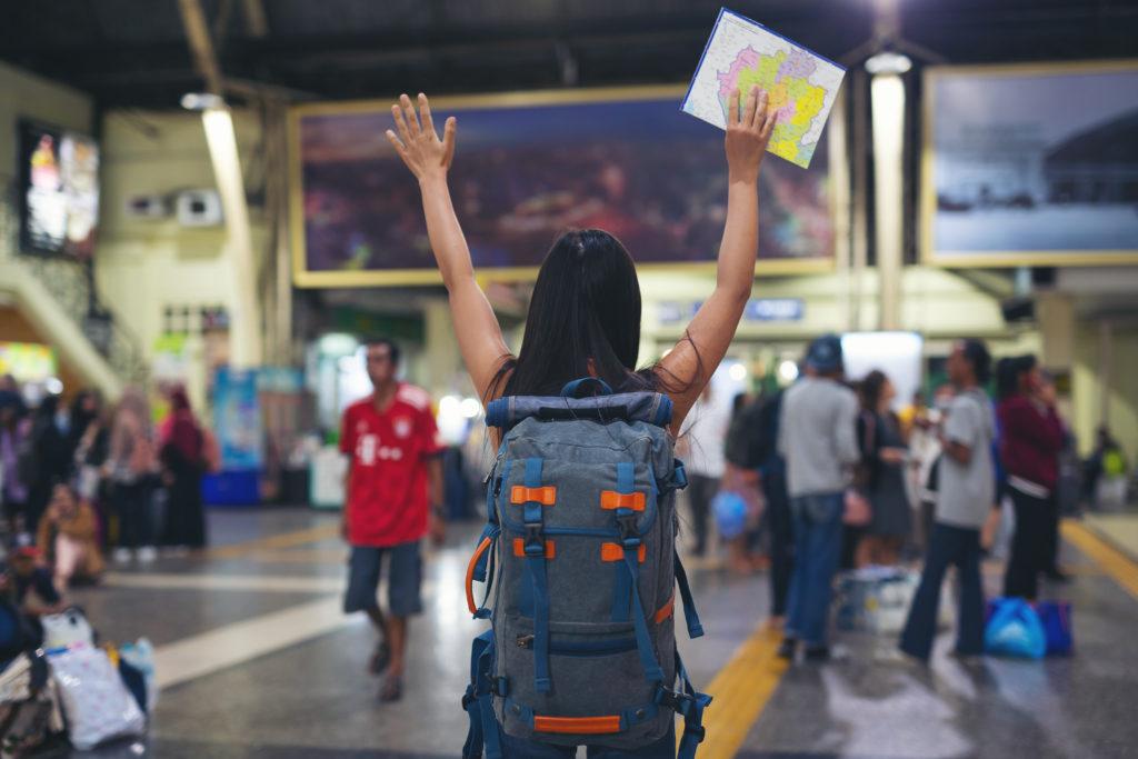 #DescriçãoDaImagem: mulher de cabelos escuros de costas com uma mochila grande e com as mãos levantadas enquanto segura um mapa.