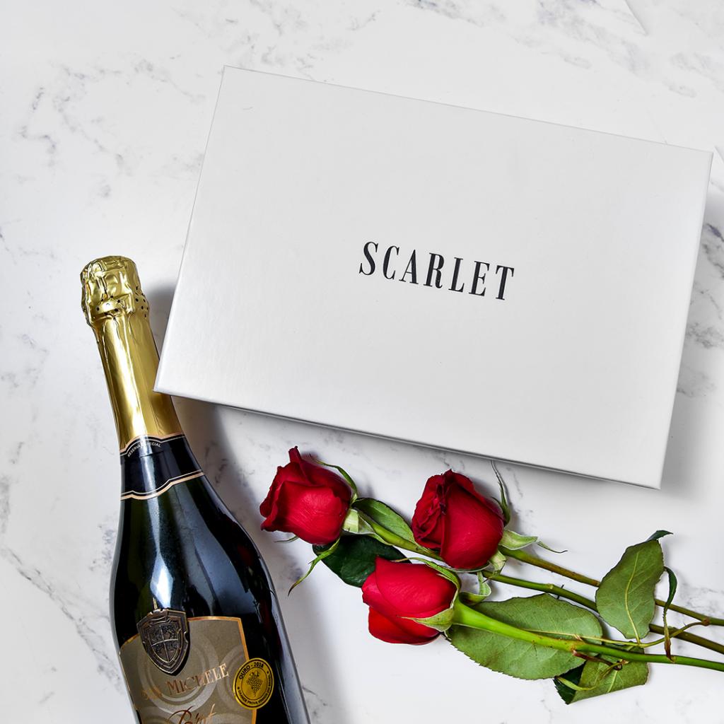 Imagem da Box Scarlet que são enviados os produtos com os elementos vinho e rosas.