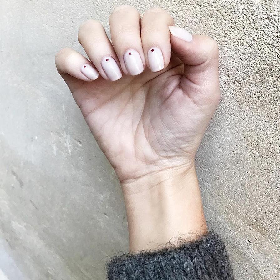 Mão com unhas pintadas de bege com pontinhos vermelhos. Fonte:@vicceridono Post: Nail art fáceis para fazer em casa